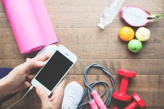 Woman in sport wear using mobile phone with fruits and sport equipments in background stock photography