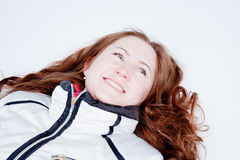 Woman in a sporting suit lies on to snow Stock Images