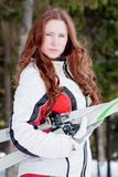 Woman in a sporting suit with skis in-field. Young woman in a sporting suit with skis in-field Royalty Free Stock Image