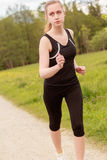 Woman in sports attire jogging Royalty Free Stock Photography