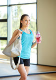 Woman with sports bag and bottle of water in gym. Fitness, sport, training, drink and lifestyle concept - happy woman with sports bag and bottle of water in gym Stock Photography