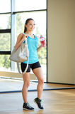 Woman with sports bag and bottle of water in gym Stock Photo