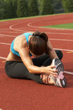Woman in Sports Bra Leaning and Stretching Leg and Hamstring Royalty Free Stock Photo