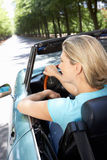 Woman in sports car. Looking away from camera Stock Photography