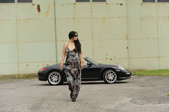 Woman with sports car. Woman walking away from sports car outdoors Royalty Free Stock Photos