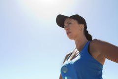 Woman in sports gear and cap with backlighting. Woman in sports gear shot from below with sun as backlight to create lens flare Stock Photo