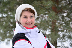 Woman in sports jacket and hat at  winter pine forest Royalty Free Stock Photos