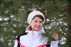 Woman in sports jacket and hat at  winter pine forest Stock Images