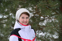 Woman in sports jacket and hat at  winter pine forest Stock Image