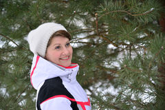 Woman in sports jacket and hat at  winter pine forest Royalty Free Stock Photo