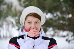 Woman in sports jacket and hat at  winter pine forest Royalty Free Stock Image