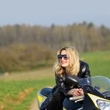 Woman on a sports motorcycle. Portrait of a beautiful blonde woman on a sports motorcycle Royalty Free Stock Images