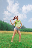 Woman sports physique in short shorts, a yellow shirt an Royalty Free Stock Photo