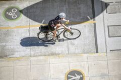 Woman in a sports uniform rides a bicycle on the cyclist lane on the pedestrian sidewalk