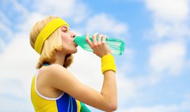 Woman in sports wear is holding a bottle of water. Sports girl drinks water from a bottle on a sky background. Healthy