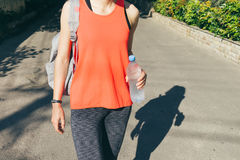Woman in sportswear with backpack holding a bottle of cold water Stock Photos