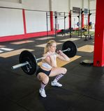 Woman In Sportswear Crouching While Lifting Barbell Stock Images