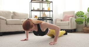 Woman doing push up at home. Woman in sportswear doing push up at home stock video footage