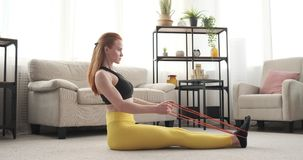 Woman doing seated row exercise with resistance band. Woman in sportswear doing seated row exercises with resistance band at home stock video footage