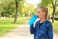 Woman in sportswear drinking protein shake. Outdoors. Space for text stock photography
