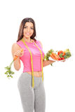 Woman in sportswear holding plate full of vegetables Stock Image