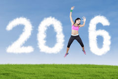 Woman with sportswear jumps with number 2016 Stock Photography