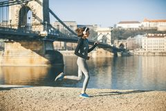 Woman in sportswear running on Danube river promenade in Budapes royalty free stock images