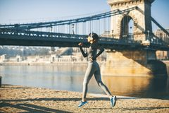 Woman in sportswear running on Danube river promenade in Budapest royalty free stock photography