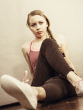 Woman in sportswear sitting on ground Royalty Free Stock Photo