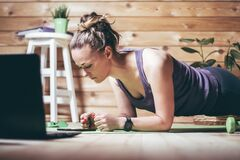 Woman in sportswear stands in plank near laptop. Home workout concept