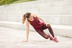 Woman in sportswear suffering from knee pain. On stairs royalty free stock photo