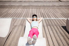Woman in sportswear on the sunbed. Young woman in sportswear resting after the training lying on the modern sunbed in the city Stock Images