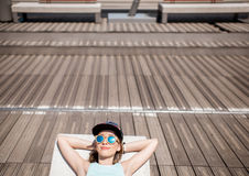 Woman in sportswear on the sunbed. Young woman in sportswear resting after the training lying on the modern sunbed in the city Royalty Free Stock Photography