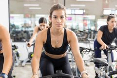 Woman In Sportswear Using Stationary Bicycle In Health Club stock photo