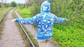 A woman in sportswear is walking on the rails of a railroad prowling.