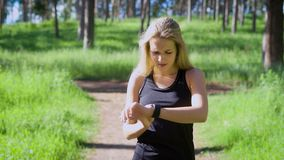 Woman in sportswear watching on watch while jogging in green wood stock video