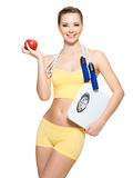 Woman with sporty body holding scales and apple Royalty Free Stock Photo