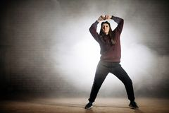 Woman in sporty clothers with raised hands posing to the camera on the street. Being good at dancing Stock Photo