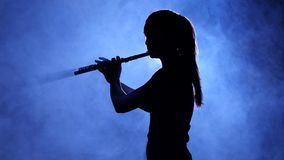 Woman in spotlight in smoky studio plays on flute, silhouette. Woman in spotlight in smoky studio plays on flute, dark silhouette of girl in smoke is visible to stock video