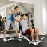 Woman spotting man at gym Stock Image