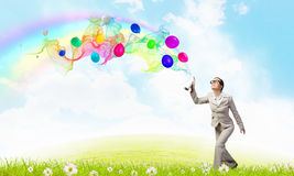 Woman spray balloons. Young woman in suit spraying colorful balloons as celebration concept Stock Photos