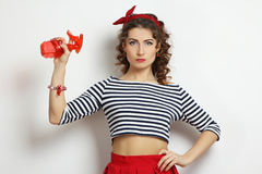 Woman with a spray. Gun on a neutral background. Pin-up style stock image