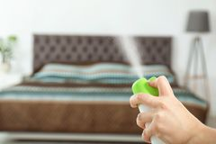 Woman spraying air freshener. In bedroom royalty free stock photography