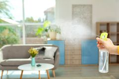 Woman spraying air freshener. At home royalty free stock photography