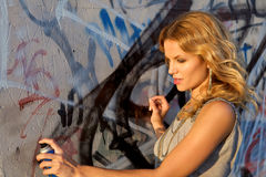 Woman spraying graffiti on a wall Royalty Free Stock Images