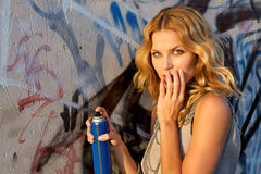 Woman spraying graffiti on a wall Stock Photo