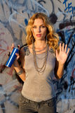 Woman spraying graffiti on a wall Stock Photography