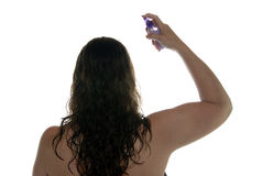 Woman spraying hair with styling product. Woman spraying hair with styling product on white background arm higher Royalty Free Stock Image