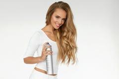 Woman Spraying Hairspray On Beautiful Curly Hair. Hairdressing. Hairstyle. Woman Spraying Hairspray On Beautiful Long Curly Hair On White Background. Attractive stock photo
