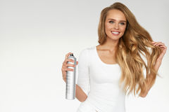 Woman Spraying Hairspray On Beautiful Curly Hair. Hairdressing. Hairstyle. Woman Spraying Hairspray On Beautiful Long Curly Hair On White Background. Attractive Royalty Free Stock Photo
